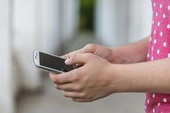 Adolescente que usa el teléfono elegante móvil Imagen de archivo