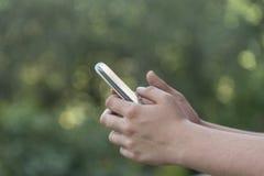 Adolescente que usa el teléfono elegante móvil Imágenes de archivo libres de regalías