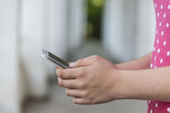 Adolescente que usa el teléfono elegante móvil Imagenes de archivo