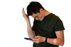 Adolescente que usa el teléfono móvil, él consigue malas noticias Imagen de archivo libre de regalías