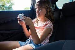 Adolescente que usa el teléfono móvil en el asiento trasero del coche Foto de archivo