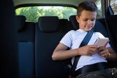 Adolescente que usa el teléfono móvil en el asiento trasero del coche Imagenes de archivo