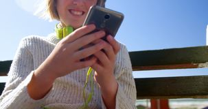 Adolescente que usa el teléfono móvil en la playa 4k almacen de metraje de vídeo