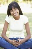 Adolescente que usa el teléfono móvil en parque Fotografía de archivo libre de regalías