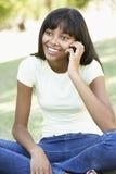 Adolescente que usa el teléfono móvil en parque Foto de archivo libre de regalías