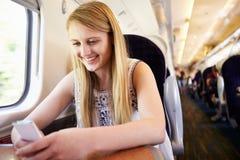 Adolescente que usa el teléfono móvil en viaje de tren Fotos de archivo libres de regalías