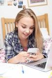 Adolescente que usa el teléfono móvil mientras que hace la preparación Imágenes de archivo libres de regalías