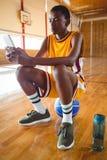 Adolescente que usa el teléfono móvil mientras que se sienta en bola Fotos de archivo