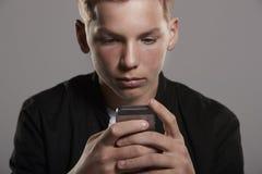 Adolescente que usa el teléfono móvil, principal y los hombros, cosecha Imágenes de archivo libres de regalías