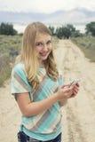 Adolescente que usa el teléfono móvil que camina abajo de un camino de tierra del país Fotos de archivo libres de regalías