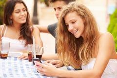 Adolescente que usa el teléfono móvil que se sienta en el ½ del ¿de Cafï con los amigos Fotos de archivo