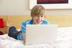 Adolescente que usa la computadora portátil en dormitorio Imágenes de archivo libres de regalías