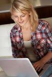 Adolescente que usa la computadora portátil en el país Foto de archivo