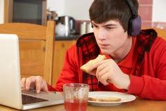 Adolescente que usa la computadora portátil mientras que come el desayuno Imágenes de archivo libres de regalías