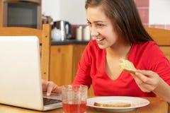 Adolescente que usa la computadora portátil mientras que come el desayuno Fotos de archivo libres de regalías