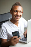 Adolescente que usa la computadora portátil y el móvil en el país Fotos de archivo