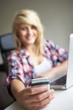 Adolescente que usa la computadora portátil y el móvil en el país Imagen de archivo