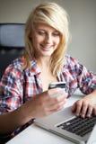 Adolescente que usa la computadora portátil y el móvil en el país Imagen de archivo libre de regalías