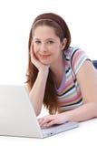 Adolescente que usa la sonrisa de la computadora portátil Fotos de archivo