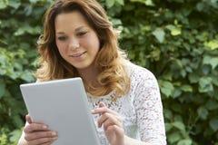 Adolescente que usa la tableta de Digitaces al aire libre Fotografía de archivo libre de regalías