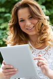 Adolescente que usa la tableta de Digitaces al aire libre Imagen de archivo libre de regalías
