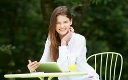 Adolescente que usa la tableta de Digitaces en café al aire libre Fotografía de archivo