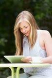 Adolescente que usa la tableta de Digitaces en café al aire libre Imágenes de archivo libres de regalías