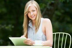 Adolescente que usa la tableta de Digitaces en café al aire libre Imagen de archivo libre de regalías