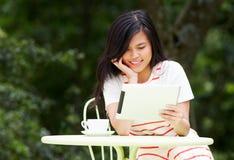 Adolescente que usa la tableta de Digitaces en café al aire libre Imagenes de archivo