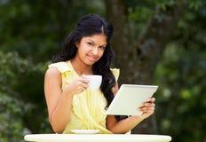 Adolescente que usa la tableta de Digitaces en café al aire libre Foto de archivo libre de regalías