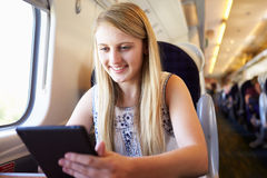 Adolescente que usa la tableta de Digitaces en viaje de tren Foto de archivo