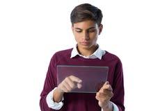 Adolescente que usa la tableta digital de cristal contra el fondo blanco Fotografía de archivo