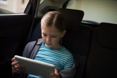 Adolescente que usa la tableta digital en el asiento trasero Imagen de archivo libre de regalías