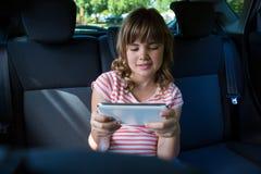 Adolescente que usa la tableta digital en el asiento trasero del coche Fotos de archivo libres de regalías