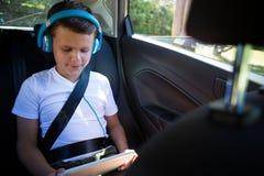 Adolescente que usa la tableta digital en el asiento trasero del coche Imagenes de archivo