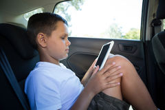 Adolescente que usa la tableta digital en el asiento trasero del coche Fotografía de archivo libre de regalías