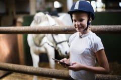 Adolescente que usa la tableta digital en el establo Fotos de archivo libres de regalías