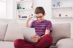 Adolescente que usa la tableta digital en el sofá en casa Imágenes de archivo libres de regalías