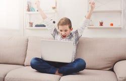 Adolescente que usa la tableta digital en el sofá en casa Fotos de archivo libres de regalías