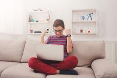 Adolescente que usa la tableta digital en el sofá en casa Imagen de archivo
