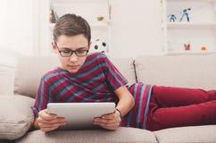 Adolescente que usa la tableta digital en el sofá en casa Imagen de archivo libre de regalías