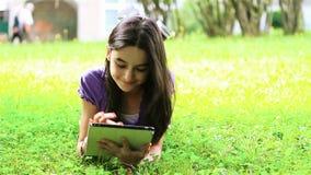 Adolescente que usa la tableta digital en hierba metrajes