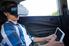 Adolescente que usa las auriculares de la realidad virtual con la tableta digital Imagenes de archivo