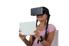 Adolescente que usa las auriculares de la realidad virtual y la tableta digital Foto de archivo