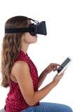 Adolescente que usa las auriculares de la realidad virtual y la tableta digital Imagenes de archivo