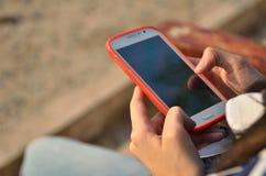 Adolescente que usa los teléfonos elegantes Imagen de archivo