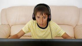 Adolescente que usa o portátil Adolescente viciado do jogo de vídeo com os fones de ouvido colados à tela do caderno que pression filme