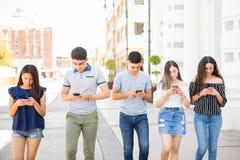 Adolescente que usa o telefone ao andar fora imagem de stock