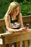 Adolescente que usa o telefone de pilha Fotografia de Stock Royalty Free