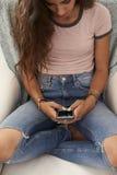 Adolescente que usa smartphone en casa, visión elevada Imagenes de archivo